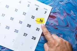 Hand pointing to Daylight Saving day on 14th March. March 2021 monthly calendar