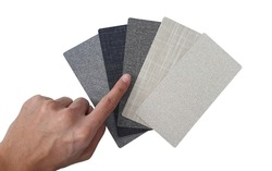 hand pointing to fabric laminateds swatch containing various textures and colors of fabric for example beige herringbone ,black linen ,grey wool isolated on white background with clipping path.