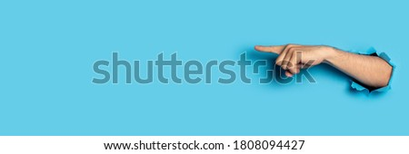 Hand points to something on a blue background. Gesture look at this, pay attention Foto stock ©