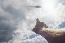 Hand points to the UFO in the sky. The day of the UFO concept of a conspiracy