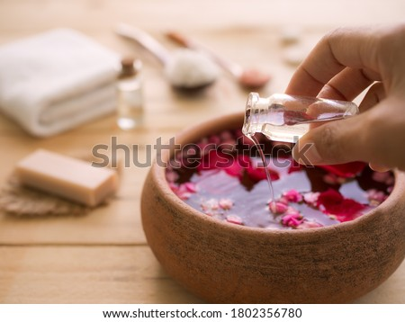 Hand pour coconut oil in to aroma smell rose with blur image of soap, towel, massage oil, salt spa on wood background.  Aroma therapy spa set for luxury hotel or professional massage salons concept.