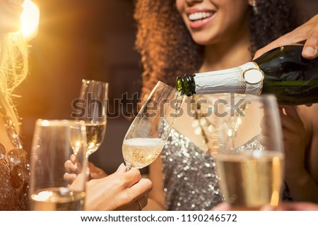 Hand pouring champagne from bottle into glasses with friends around him. Closeup of hand pouring white wine in flutes during party. Detail shot of new year's eve celebration.