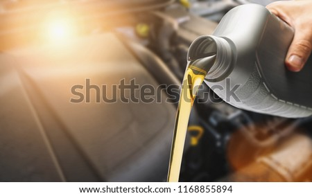 Hand Pouring oil to car engine, Fresh oil poured during an oil change to a car.