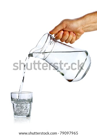 Hand pouring water from glass jug to glass against white background