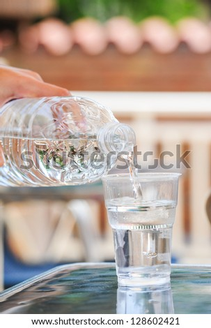 Hand pouring water on a glass.Bottle pouring water into a plastic glass.Drinking water pouring into glass outdoor.