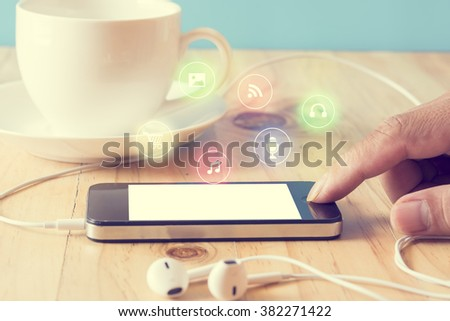 Hand press smart phone with ear phone and coffee cup on the table,vintage filter
