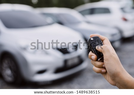 Hand presses on the remote control car alarm systems. #1489638515