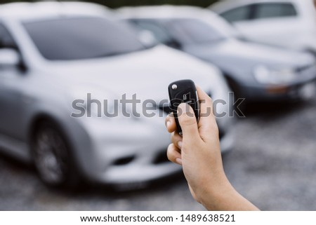 Hand presses on the remote control car alarm systems. #1489638521