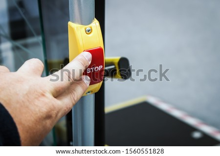 hand presses stop button in modern bus, electric bus or tram #1560551828