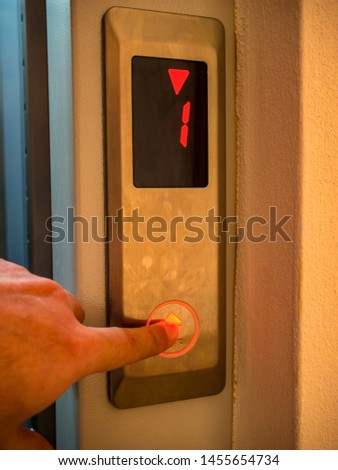 Hand presses the button of the elevator call #1455654734
