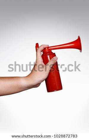 Hand pressing an air horn metal can #1028872783