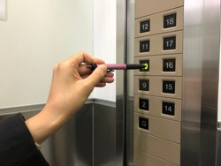 Hand pressing an elevator button with a pen. Touchless is an effective method of infection control.