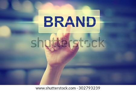 Hand pressing BRAND button on blurred cityscape background