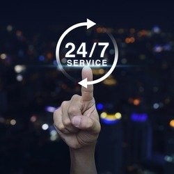 Hand pressing button 24 hours service icon over blurred light city tower background, Full time service concept