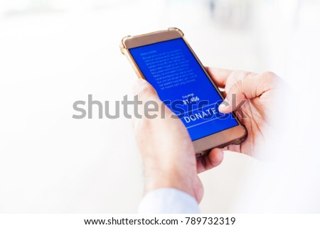 """Hand pressing """"Donate"""" button on the screen of smartphone"""