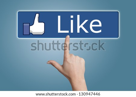 Hand pressing Like button on blue background
