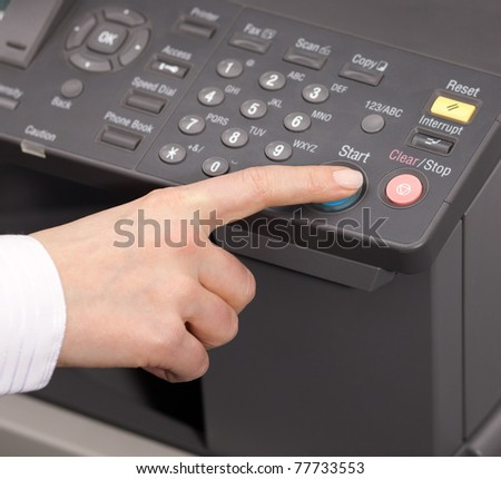Hand pressing Start button on copy machine