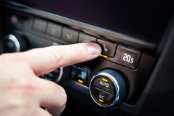 Hand pressing the button for heated seats in the car