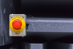 Hand pressing the red emergency button or stop button for industrial machine, Emergency Stop for Safety.