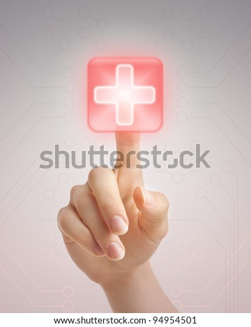Hand pressing virtual button with first aid sign.