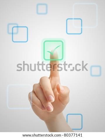 Hand pressing virtual green tick button on futuristic holographic screen.