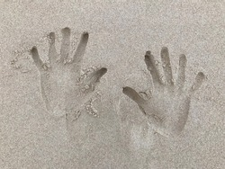 Hand print engraved in sand at the beach