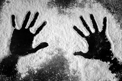 Hand prints in flour on dark background