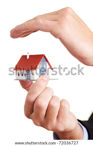 Hand protecting a small miniature house with a roof