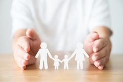 Hand protecting family on wood table. Healthcare and life insurance concept