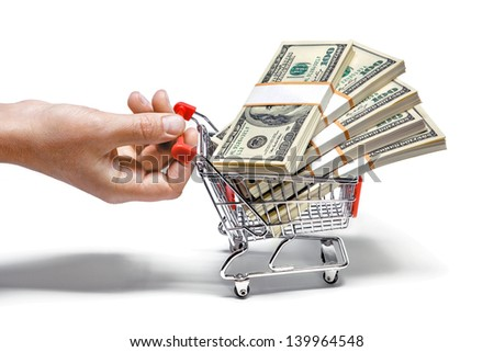 hand pulling shopping cart full of stacks of dollar bills isolated on white