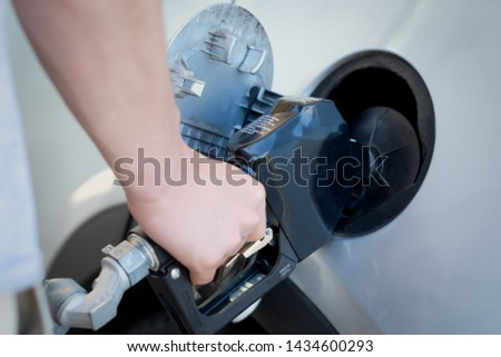 Hand pumping gasoline at the gas station