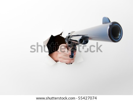 Hand punching through a white paper background with big revolver. Photographed with a fisheye lens for exaggerated perspective.