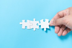 Hand push a piece of jigsaw puzzle to complete the mission for business merging concept or coorperate acquisition