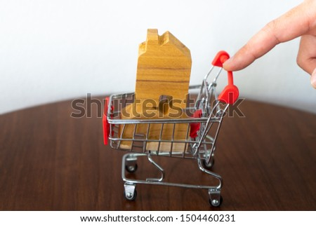 Hand push shopping trolley basket or cart with house  in pushcart.Choose  housing loan that right.Home  exhibition.