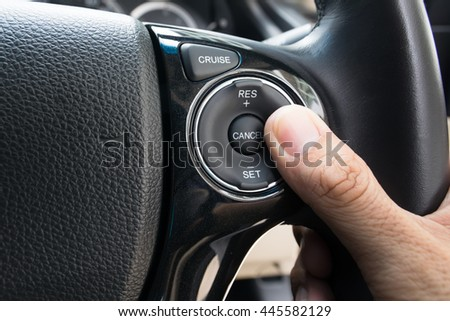 hand pushes Cruise control buttons on modern car and speed limitation
