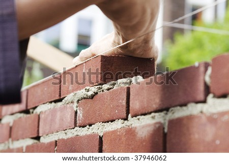 Hand pushes down brick in cement building a wall - stock photo