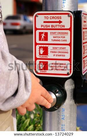Hand pushing a crosswalk button at a traffic signal
