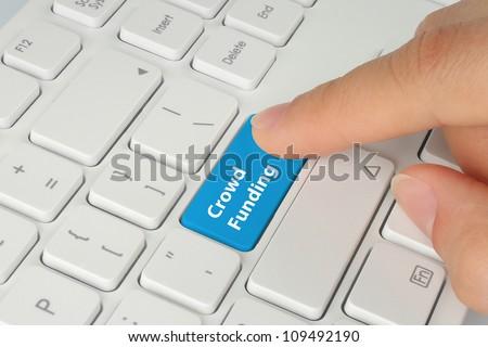 Hand pushing blue crowd funding button on keyboard