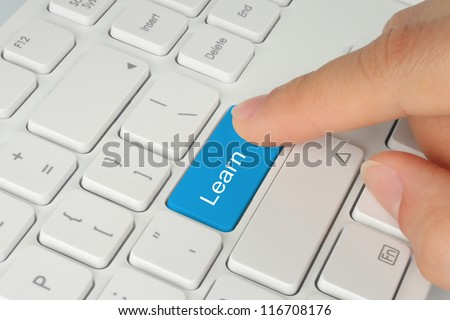 Hand pushing blue learn keyboard button