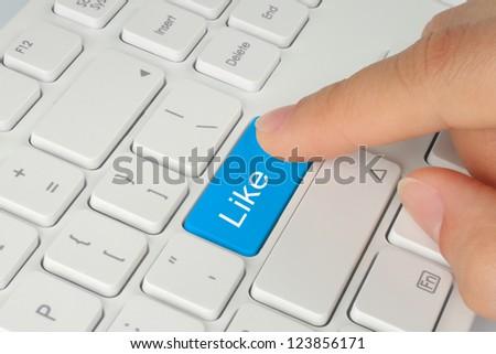 Hand pushing blue like button on keyboard close-up