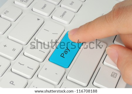 Hand pushing blue pay keyboard button - stock photo