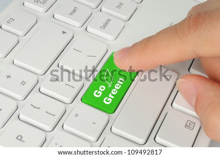 Hand pushing go green button on keyboard - stock photo