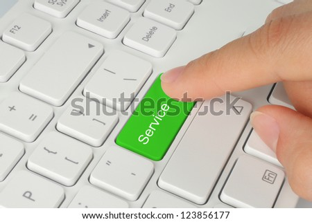 Hand pushing green service button of the keyboard