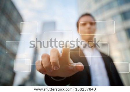 hand pushing on a touch screen interface on business buildings background