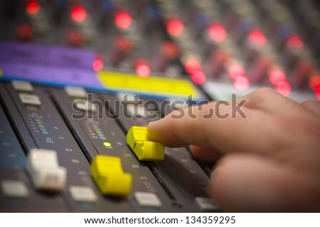 Hand pushing open a fader on a sound desk with narrow depth of field.
