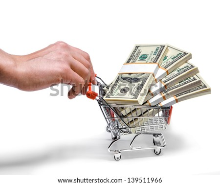 hand pushing shopping cart full of stacks of dollar bills isolated on white