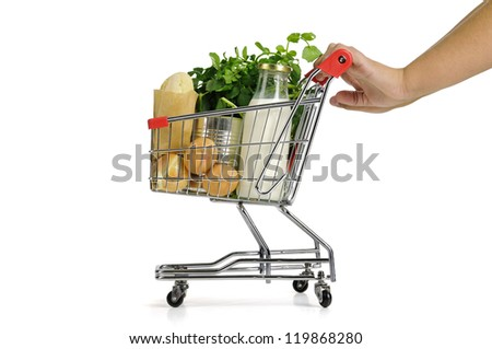 Hand pushing small shopping cart full with groceries  isolated in white