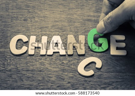Hand put a letter into the word for Change concept