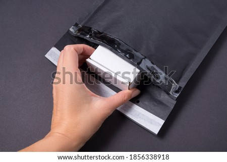 Hand put cardboard box to black paper bubble envelope  Foto d'archivio ©
