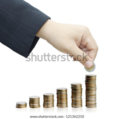 Hand put coin to money staircase, increasing columns of coins isolated on white background.